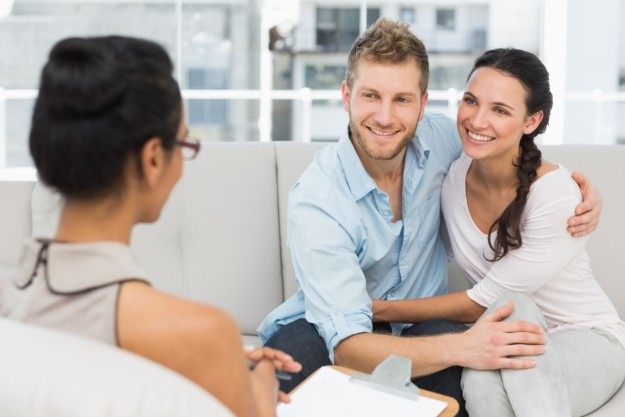 Smiling couple reconciling at therapy session